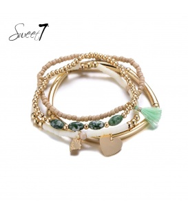 Set van armbanden met naturelkleurige kralen en een groen kwastje